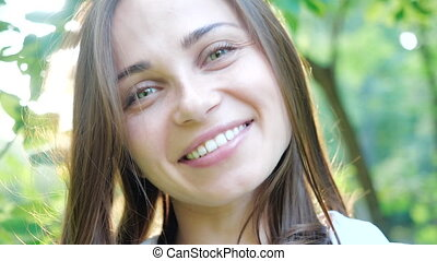 Close view of the beautiful face of young woman posing and smiling at the camera lens. Photoshoot in a warm sunny park for a pretty girl with green eyes, close-up shot of the face. Wind blows on hair.