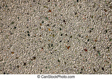 Close view of the textured background of a cement wall mixed with broken glass.