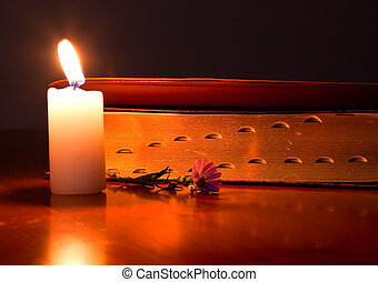 Closed Bible by candle light lying on a wooden table with small flower