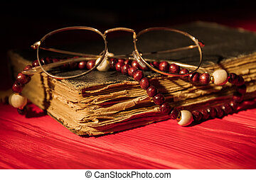 Closed Bible With Rosary And Glasses.