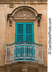 Closed blue window shutters and a small balcony