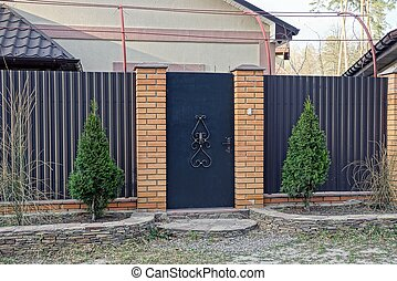 closed brown door and part of a fence with coniferous green ornamental trees
