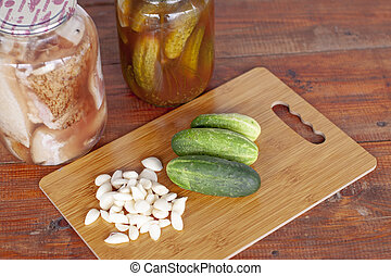 Closed cucumbers and closed pieces of lard with meat in glass jars for the winter. Chopping board with cucumbers and garlic slices