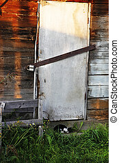 Closed door with old lock on village farm house. Storage building is closed with lock. Closed house. Cat is sleeping before door.