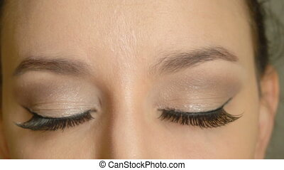 Closed eyes and long false eyelashes on female face. Closeup...