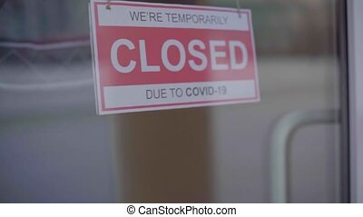 Closed for business due to covid. Small shop puts closed sign up on storefront. Slow motion.