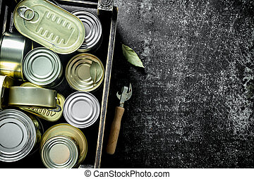 Closed metal cans with canned food in the box.