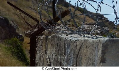Closed old object - Barrier of wall and barbed wire against...