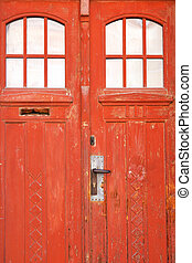 Closed old red door with blanched paint
