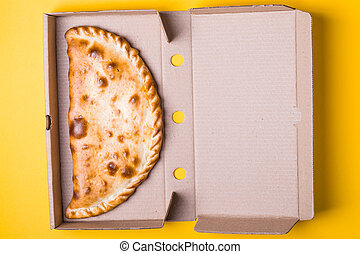 Closed pizza calzone in a packing box on a yellow background