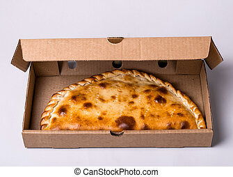 Closed pizza calzone in packing box on gray background