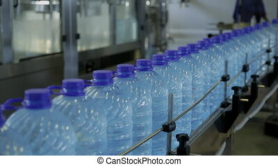 Closed plastic water bottles roll along conveyor belt of container.