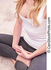 Woman sitting on carpet in lotus pose
