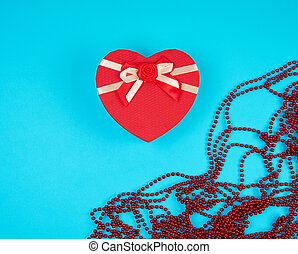 red gift box in the form of a heart with a bow