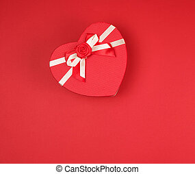 gift box in the form of a heart with a bow on a red background
