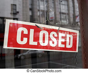 Closed sign in a shop showroom with reflections - red sign over desaturated background