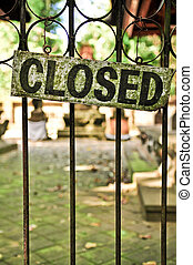 Closed sign on the metal door bars