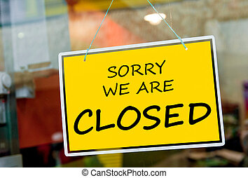 sorry we are closed sign hanging on a window door outside a restaurant, store, office or other