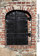 closed traditional iron door on brick wall