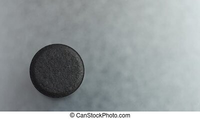Closed up Activated charcoal carbon pill slow motion turning on a metal background, top view.