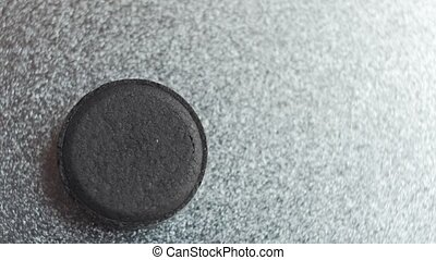 Closed up Activated charcoal carbon pill turning on a metal background. Top view.