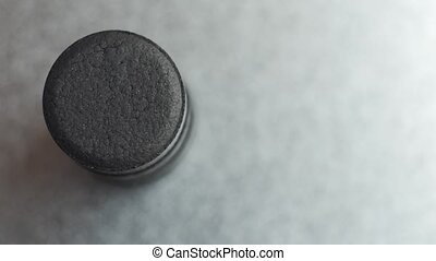 Closed up Activated charcoal carbon pills turning on a metal background, top view.