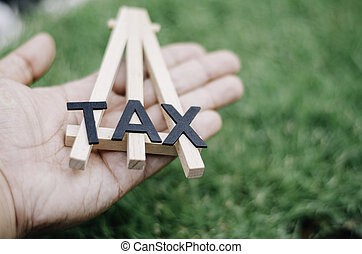 closed up and cropped image, hand hold black word alphabetical TAX on wooden tripod. green grass and soft bokeh. retro look image