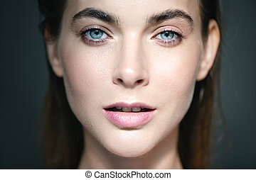 Closed up portrait of beautiful young woman with drops of water on her face