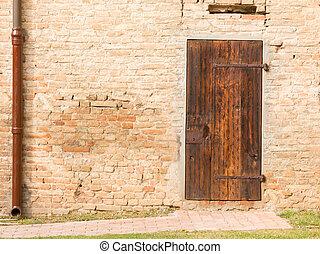 Closed vintage wooden door on brick wall