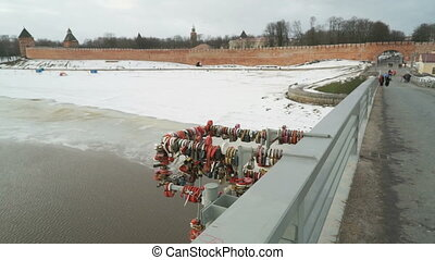 Closed wedding locks on pipes on the bridge