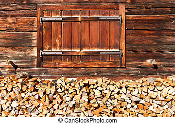 Closed window and stacked firewood of old alpine hut. Rural alpine scenery.
