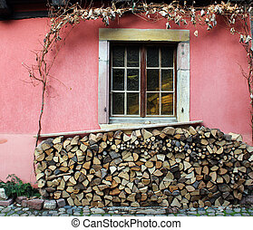 Closed window on a pink wall and a woodpile