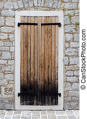 Closed wooden door in a stone wall