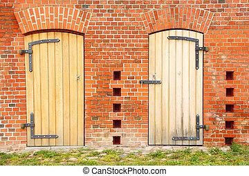 Closed wooden door in the brick wall