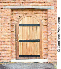 Closed wooden door with brick wall.