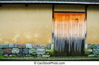 Closed wooden door with the stones wall.