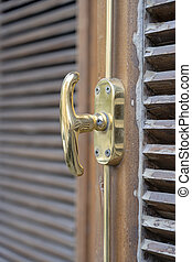 Closed wooden shutters blinds and metal window handle
