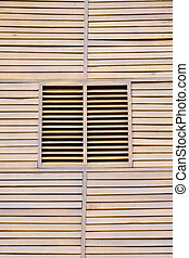 Closed wooden shutters on a wooden panneled wall.