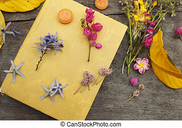 Closed yellow book with flowers and leaves still life on wood table background top view horizontal