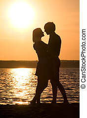Closeness - Profiles of romantic couple embracing each other...