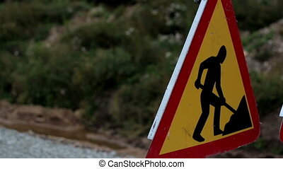 Closer image of the men working sign next to the road