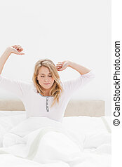 Closer shot of woman in bed sitting up with stretched out arms