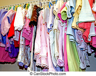 This is a closet of girl's clothing hanging in a row of various colored outfits.