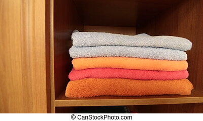 Closet shelves with stacks of clothes and bath towels