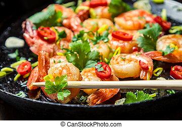 Closeu of tasting fried shrimp with chopsticks