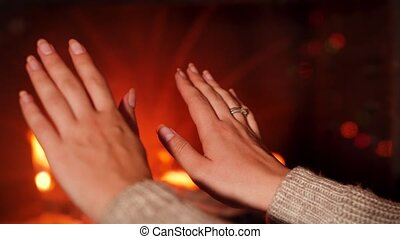 Closeup 4k foootage of young woman warming her hands at burning fire in fireplace