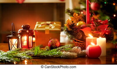 Closeup 4k footage burning candles, decorations and gifts on wooden table against Christmas tree and fireplace in living room. Perfect shot for winter celebrations and holidays