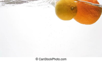 CLoseup 4k footage of assortment of citrus fruits falling in...