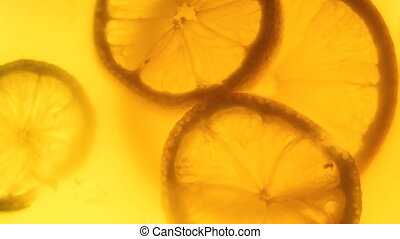 Closeup 4k footage of backlit lemonade with slices of lemons...