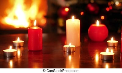 Closeup 4k footage of burning candles against fire in fireplace and glowing Christmas tree. Perfect background or backdrop for Christmas or New Year